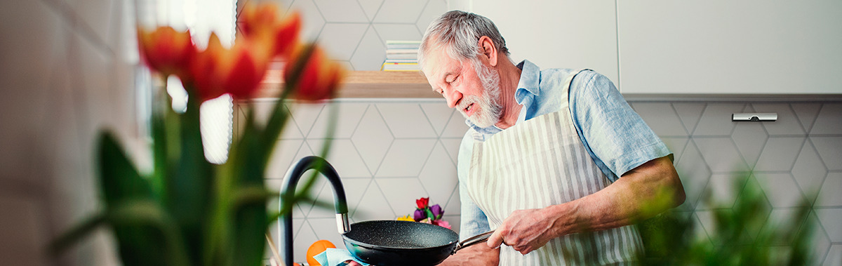 A middle-aged man in retirement living washes up his cooking pan in the kitchen, with the hob in the background protected by the Airis fire safety system