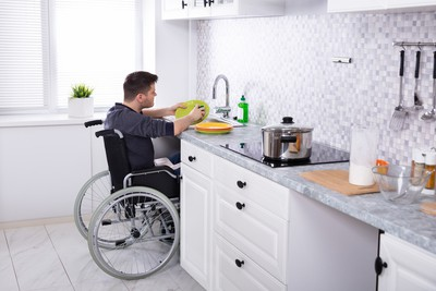 A young man in a wheelchair using the sink in his kitchen with the hob protected by the Airis fire safety device