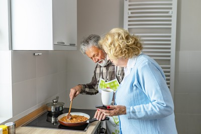 An elderly man and his relative prepare a meal together while the Airis fire prevention device protects them and the kitchen from fire and smoke