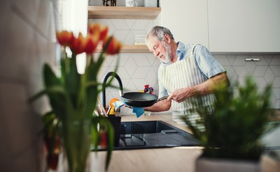 A middle-aged man in his kitchen, cleaning a frying pan with the Airis fire safety device protecting the hob in the background