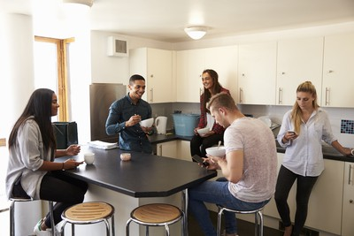 Students in a communal kitchen socialise over breakfast