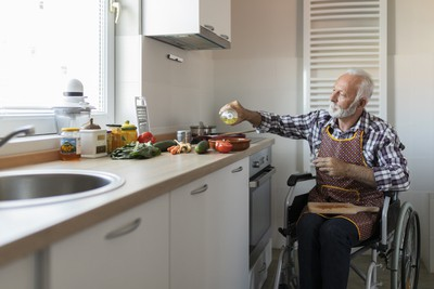 A man in a wheelchair pours oil into his pan while the Airis fire prevention device keeps him and his kitchen safe from fire